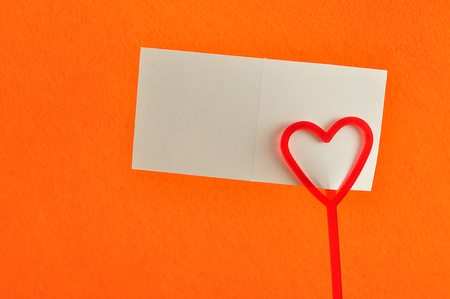 Valentines day. A note holder with a red heart with a note isolated against an orange background