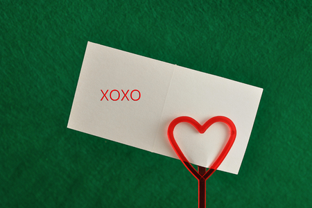Valentines day. A note holder with a red heart with a note reading xoxo isolated against a green background