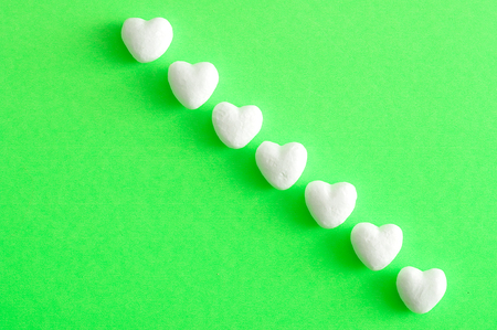 Valentines Day. White polystyrene hearts on a green background