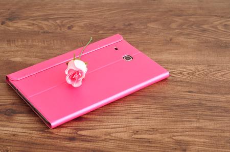 A tablet in a pink holder displayed with a pink rose Reklamní fotografie