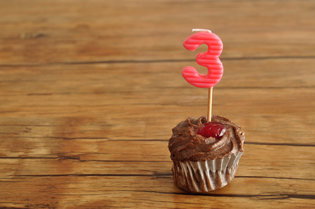 A chocolate cupcake with a birthday candle in the shape of a three displayed on a table Stock Photo