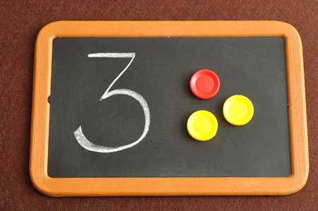 A number three written on a black board with the same quantity showed by colorful round tokens Reklamní fotografie