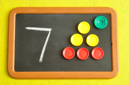 A number seven written on a black board with the same quantity showed by colorful round tokens