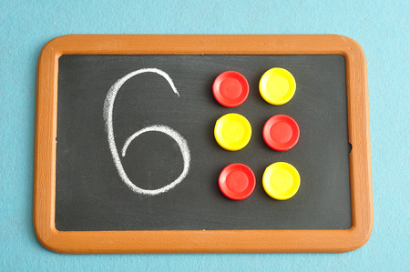 A number six written on a black board with the same quantity showed by colorful round tokens