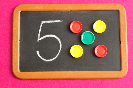 A number five written on a black board with the same quantity showed by colorful round tokens Reklamní fotografie