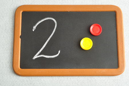 A number two written on a black board with the same quantity showed by colorful round tokens