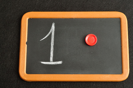 A number one written on a black board with the same quantity showed by colorful round tokens