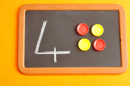 A number four written on a black board with the same quantity showed by colorful round tokens