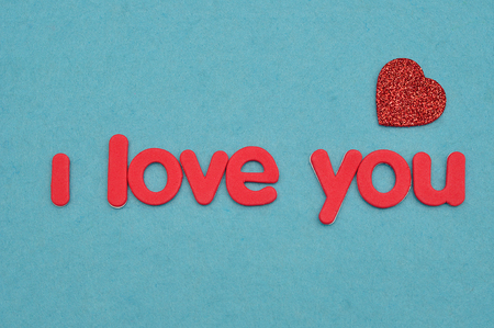 I love you in red letters on a blue background with a red heart