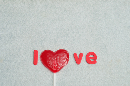 A heart shape lollipop replacing the letter o in the word love