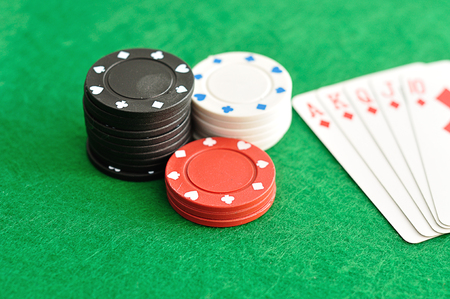 A stack of poker chips with a royal flush that is out of focus Stock Photo