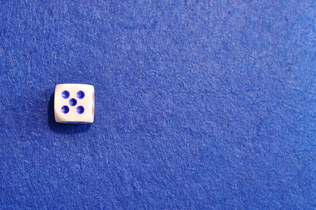 A single dice with the number five displayed on the top Stock Photo