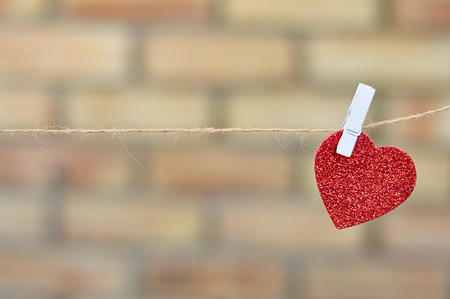 A red heart shape hanging on a rope Stock Photo