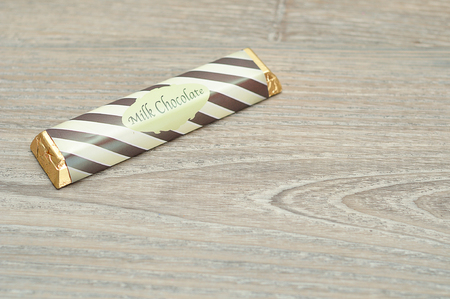A candy bar with a wrapper isolated on a wooden background