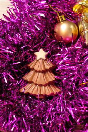 A chocolate christmas tree shape displayed with tinsel and golden Christmas tree decorations