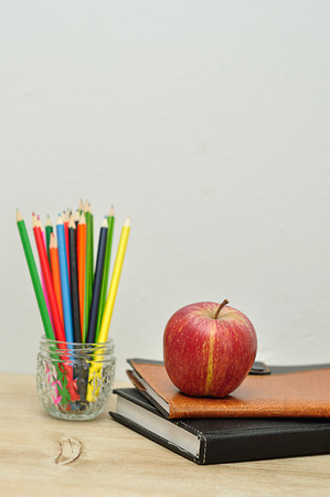 An apple displayed with books and coloring pencils