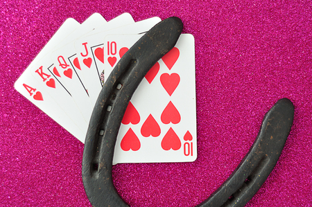 A royal flush displayed with a good luck charm, a horseshoe.