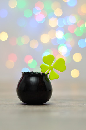 A clover in a black pot displayed against an out of focus light background
