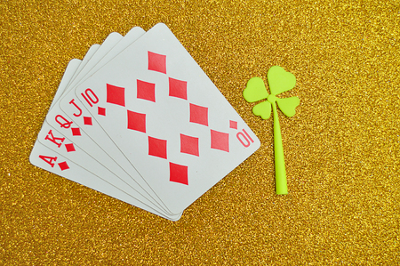 A royal flush displayed with a good luck charm, a clover.