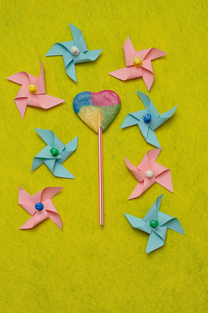 A colorful heart shape lollipop displayed with colorful pinwheels on a yellow background