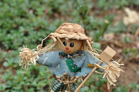 A scarecrow figurine standing in a garden