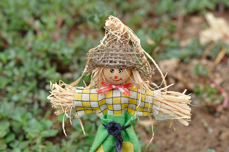 A scarecrow figurine standing in a garden