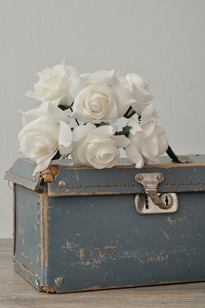 An old worn out blue suitcase with a bunch of artificial white roses Stockfoto