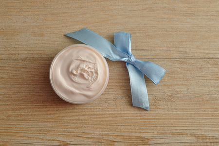 A jar of orange body lotion displayed with a blue bow