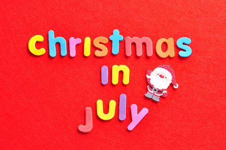 The words christmas in July in colorful letters on a red background and a Santa Clause figurine