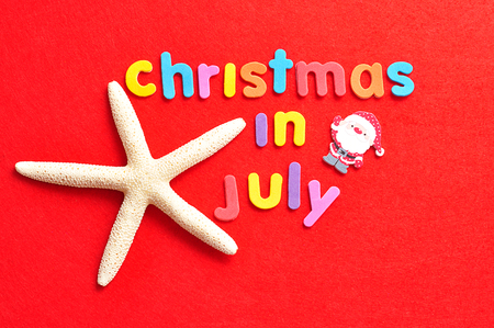 The words christmas in July in colorful letters on a red background with a starfish and a Santa figurine