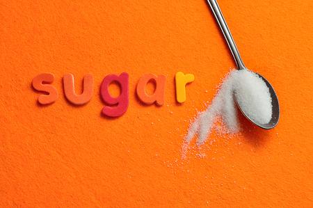 A teaspoon of sugar with the word sugar on an orange background