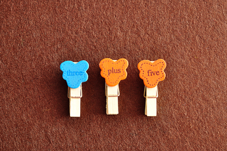 Three plus five on a brown background Stock Photo