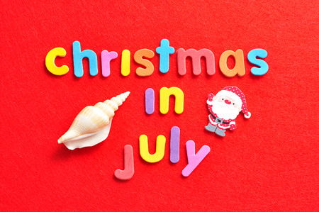 Christmas in July on a red background with a shell and a Santa Clause figure Stock Photo