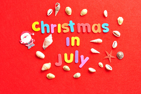 Christmas in July on a red background with a collection of shells and a Santa Clause figure