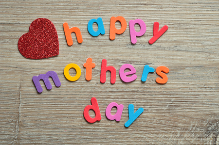 Happy mothers day in colorful letters on a wooden background with a red heart