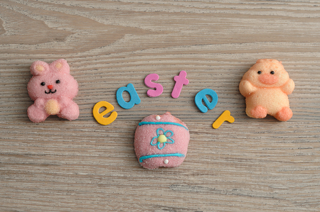 A pink bunny shape marshmallow, a chicken shape marshmallow and an egg with the word easter