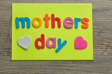 Mothers day on a yellow note with a white and a pink heart
