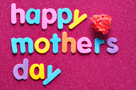 Happy mothers day on a pink background with an artificial rose