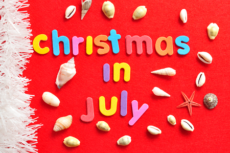 Christmas in July on a red background with a collection of shells and a string of white tinsel