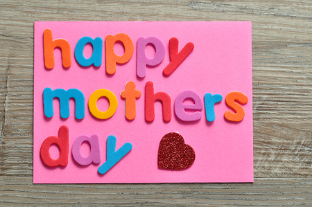 Happy mothers day on a pink note with a red heart Stock Photo