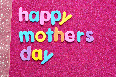 Happy mothers day on a pink background with a pink ribbon