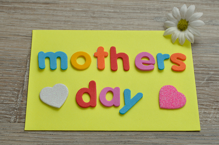 Mothers day on a yellow note with a white and a pink heart and a white daisy Stock Photo