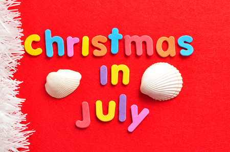 Christmas in July on a red background with shells and a string of white tinsel Stock Photo