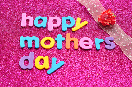 Happy mothers day on a pink background with a pink ribbon and an artificial rose Stock Photo