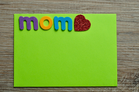 The word mom with a red heart on a green note