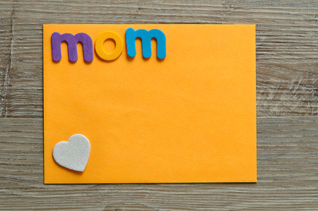 The word mom with a white heart on an orange note Stock Photo