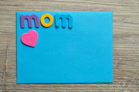 The word mom with a pink heart on a blue note