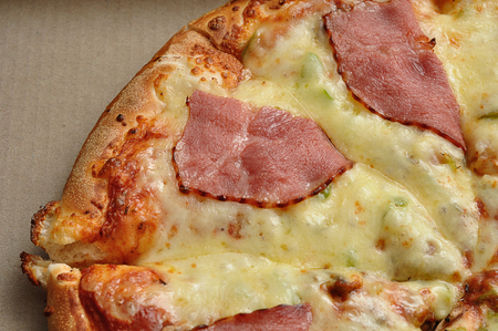 A pizza with a bacon and cheese topping