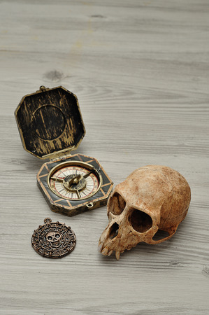 A compass and a pirate coin toy for a pirate game with a monkey skull Stock Photo