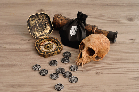 A compass, eyeglass and coins and a money bag for a pirate game with a monkey skull